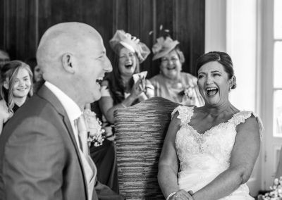 black and white photo of bride and groom laughing hysterically