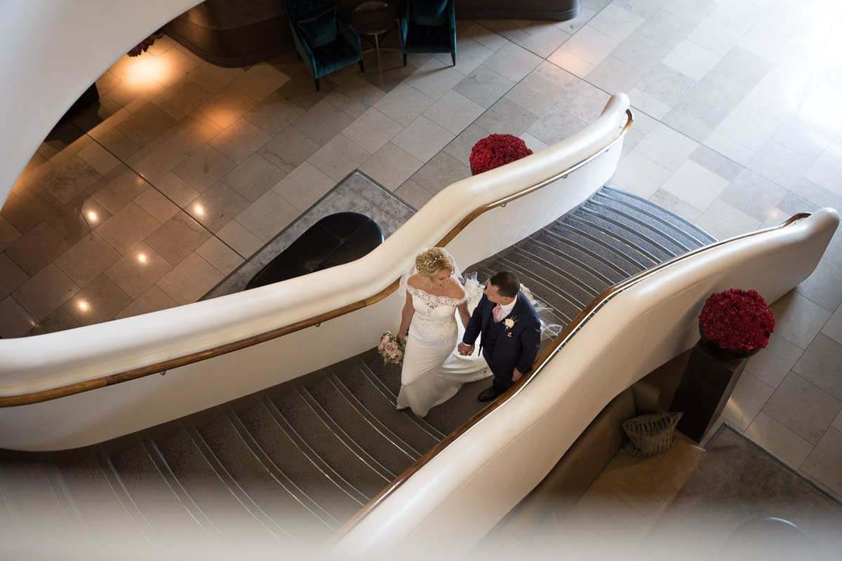 bride and groom pose on the stairs at the Aviator hotel in Farnborough