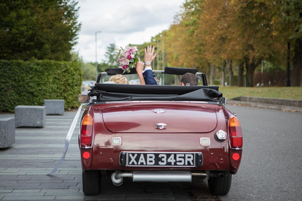 Waving bride and groom leave the Aviator hotel in their red MG car