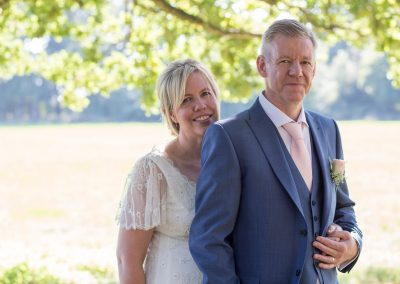 bride and groom pose under a leafy tree in the sunshine