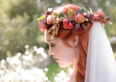 redheaded bride wearing autumnal flower crown and veil