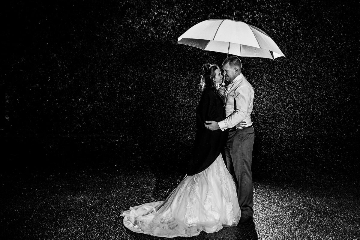 black and white photo of a bride and groom standing under an umbrella in the rain at night, with the bride wearing the groom's jacket