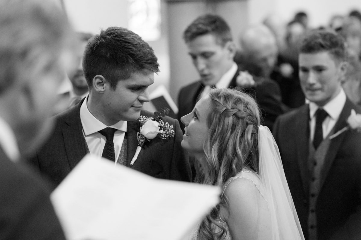 black and white of bride and groom looking at each other in church