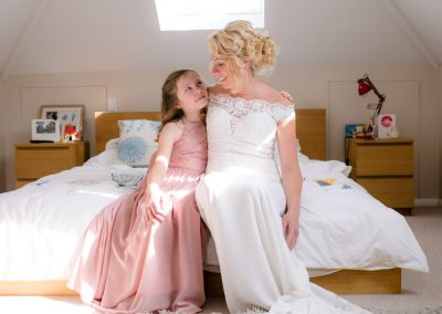 bride and bridesmaid share a moment as they sit on the bed during bridal preparations