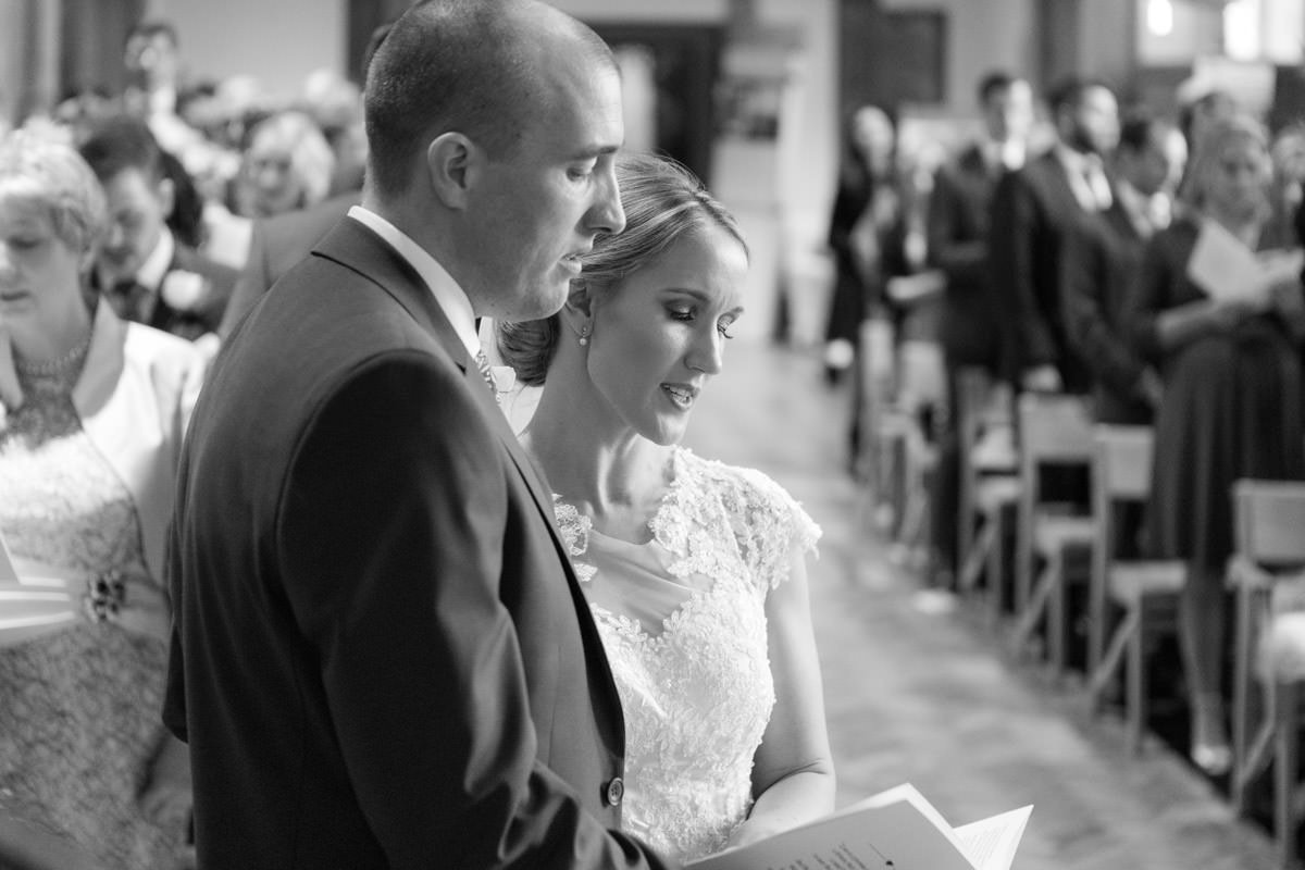 bride and groom singing together in church