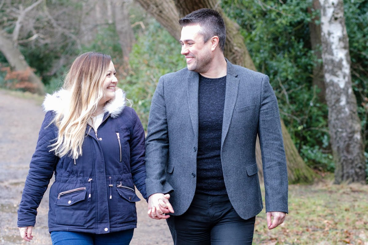 couple hold hands as they walk together and look at each other at Virginia Water