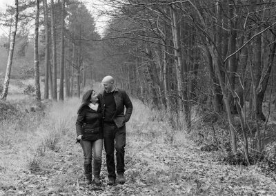 Black and white photo of couple walking together through the Swinley Forest woods