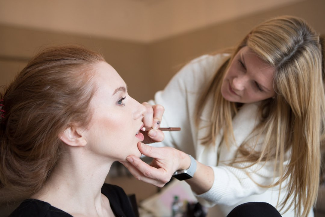 Kate Causton make up artist applies lip liner to model Scarlett Howard at Farnham castle