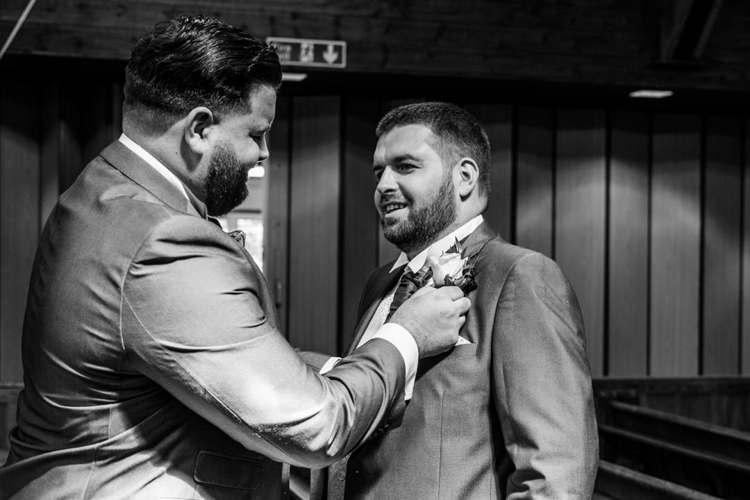 black and white of the best man helping the groom with his buttonhole in church before the ceremony