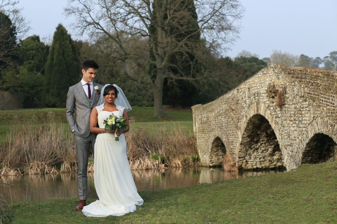 Bride and groom stand in front of the River Wey, with an old stone bridge to their left