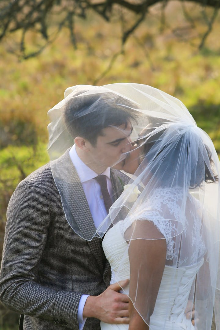 Bride and groom kiss whilst underneath her short veil
