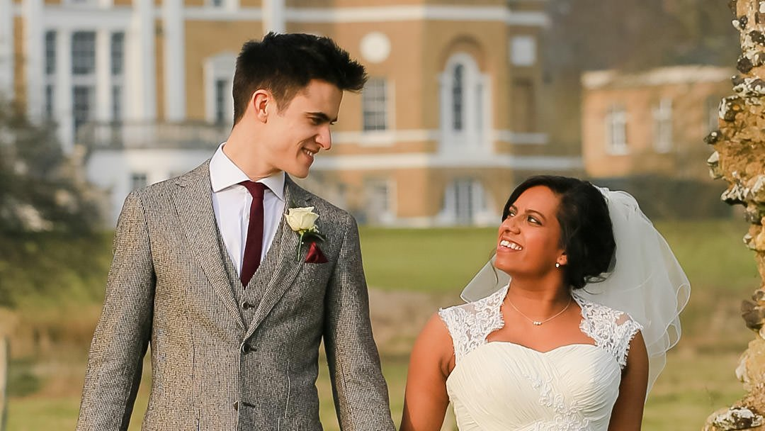 Close up of the bride and groom smiling at each other as they walk with Waverley Abbey House behind them in the distance