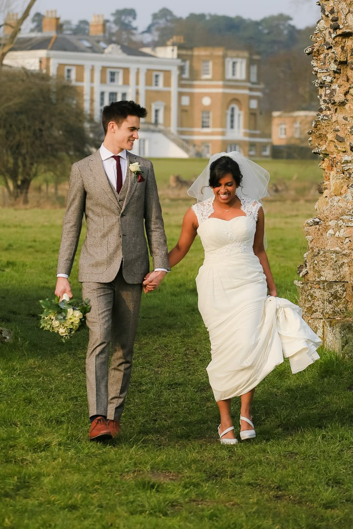 bride and groom smiling at each other as they walk with Waverley Abbey House behind them in the distance