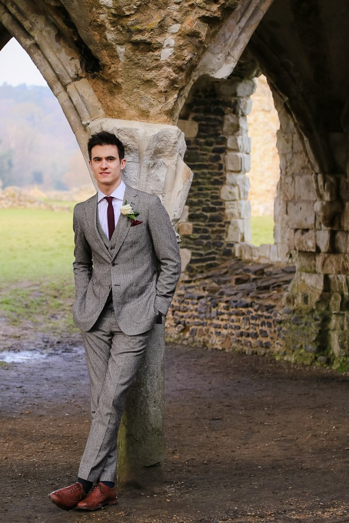 Groom with his hands in his pockets and wearing a brown tweed suit leans against the archway of a ruin