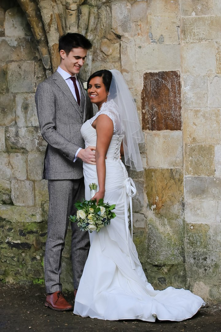 bride and groom pose together in front of an old stone wall