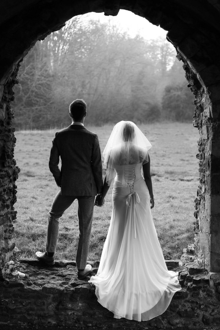 Black and white image of bride and groom standing in the ruins ofWaverley Abbey with their backs to us and looking out into a field