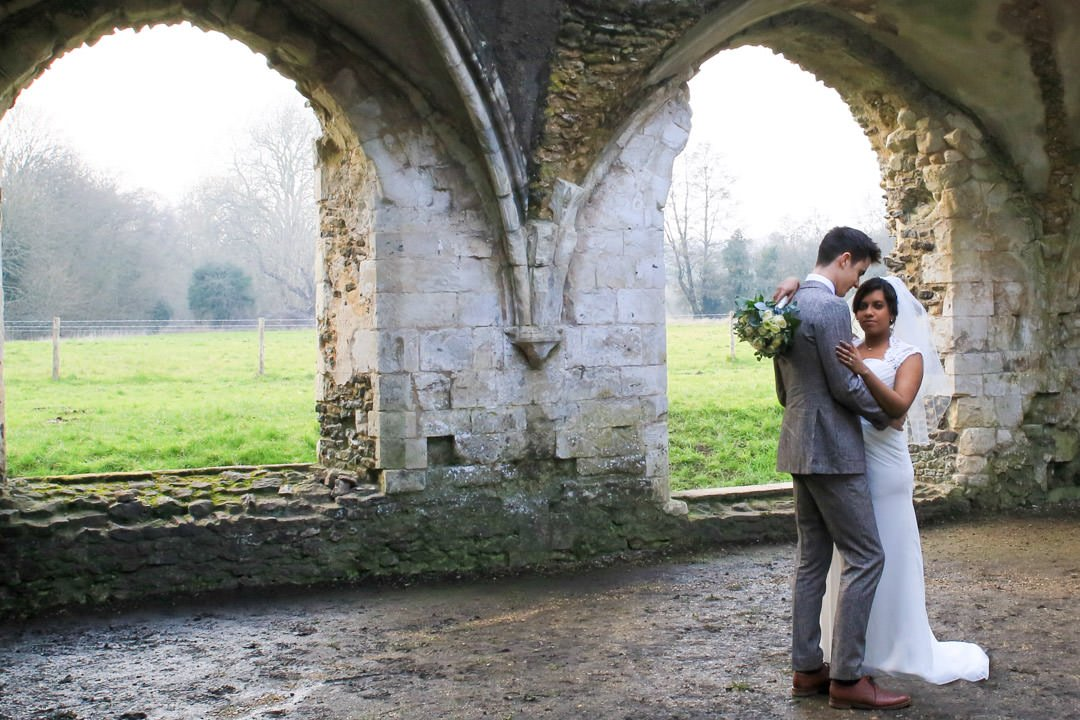 Bride and groom stand in the ruins of the Abbey
