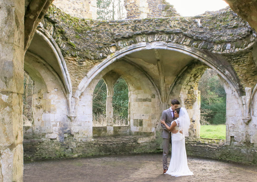 Groom kisses the bride's forehead as they embrace in the ruins of the Abbey