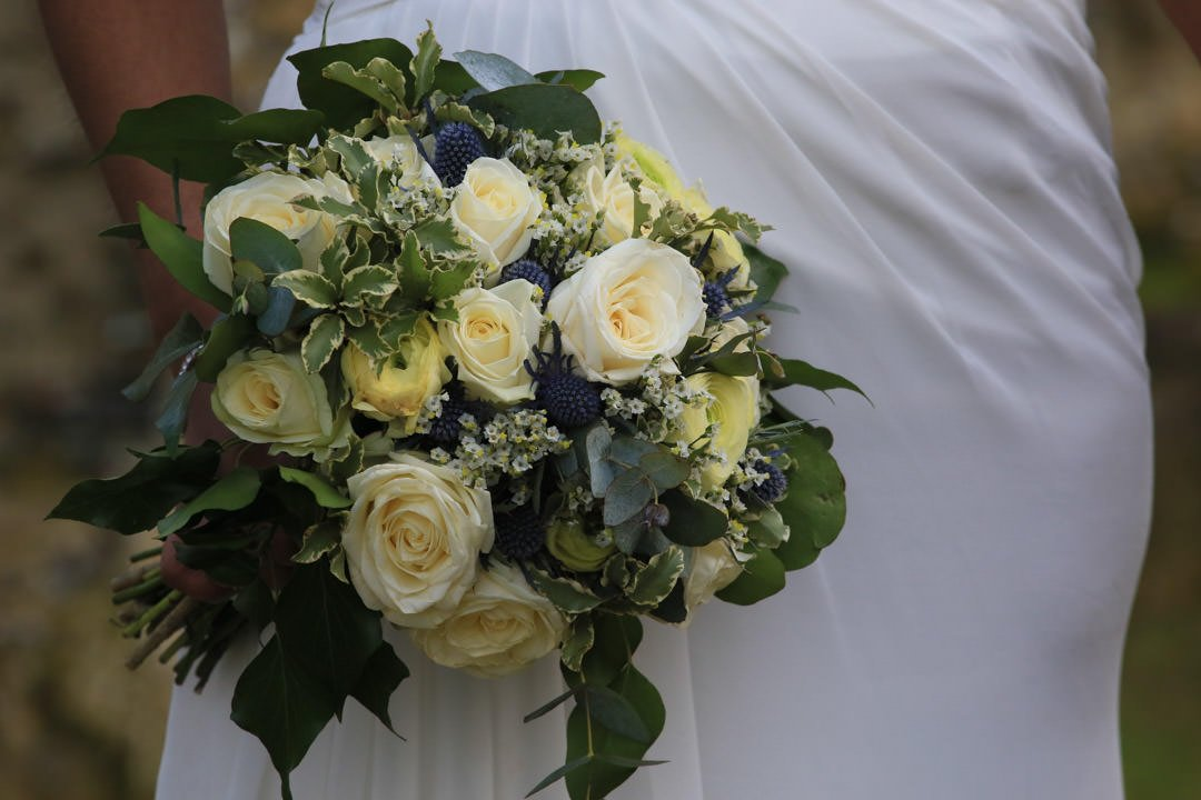 Detail shot of a bridal bouquet of cream and yellow roses, with variegated euonymus and blue sea holly