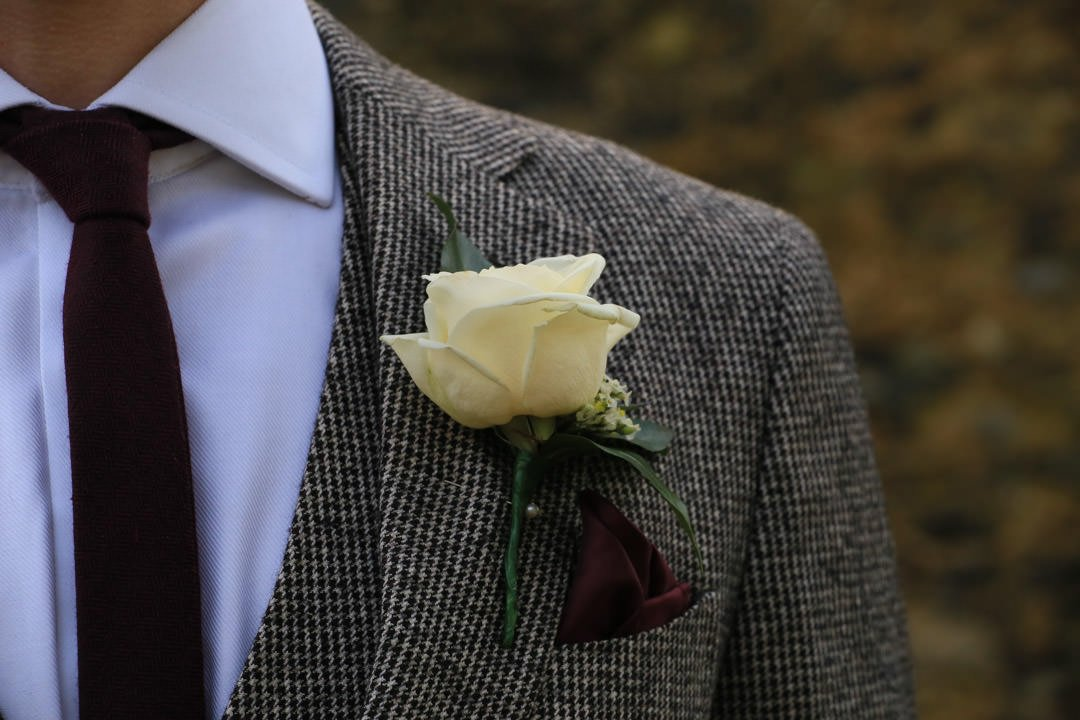 detail shot of the groom's tweed jacket and his cream rose buttonhole