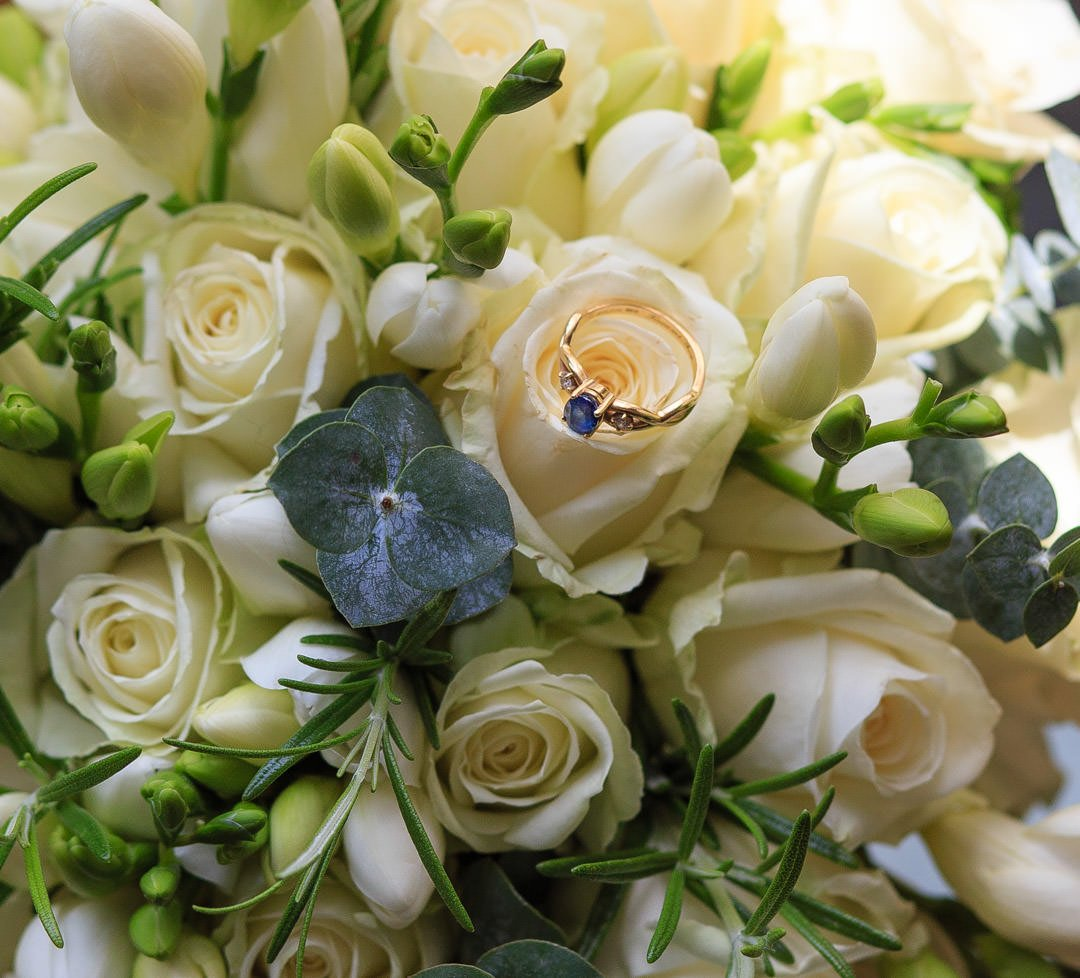 Sapphire engagement ring sits on a bouquet of cream roses, freesia, rosemary and eucalyptus