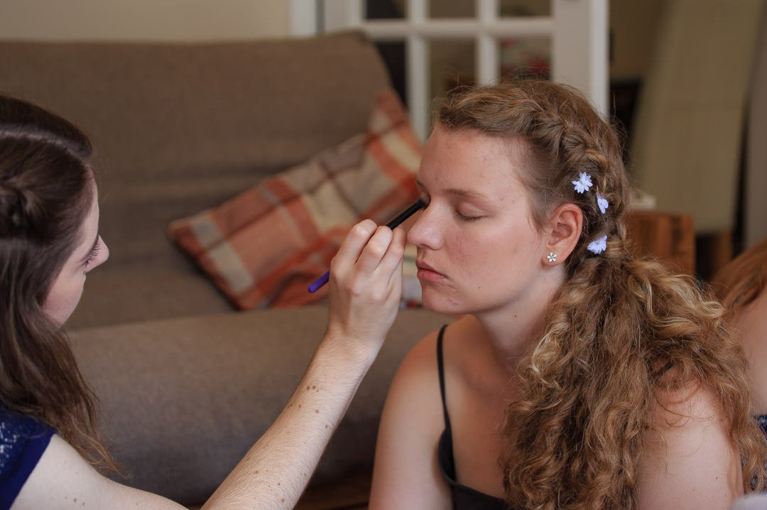Bridesmaids do each others eye makeup in preparation for the wedding
