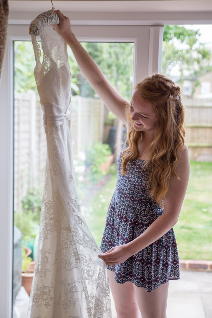 Bride holds up her wedding dress on the hanger as she looks at it
