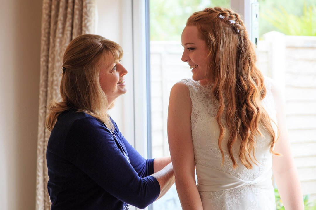 Bride and mum smile at each other as mum does up the bride's dress