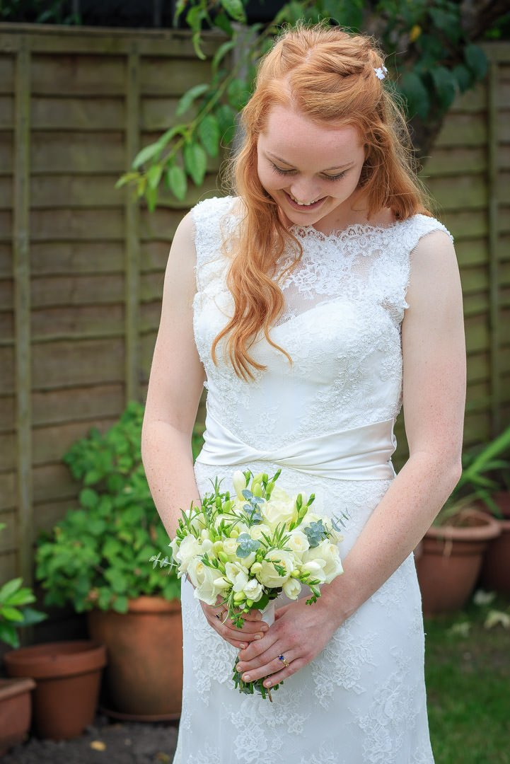 Young bride poses in the garden and looks at her bouquet of cream roses