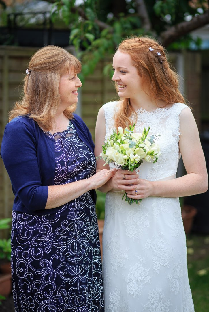 Mother holds the bride's arm as they stand together in the garden