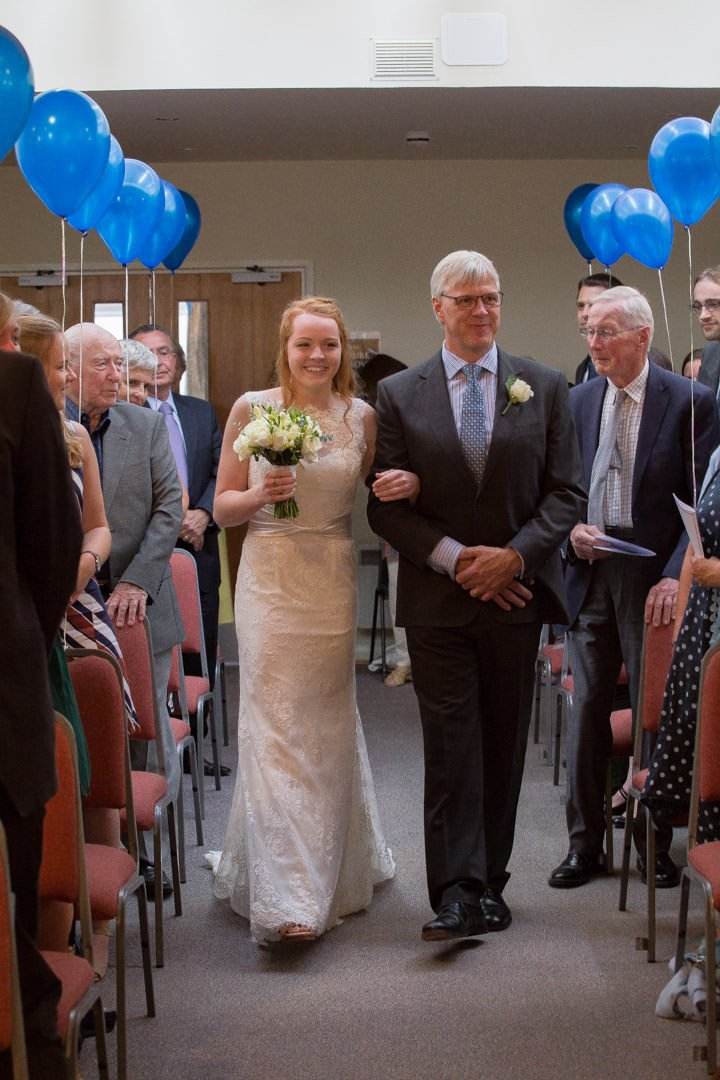 The father of the bride escorts his daughter down the aisle at Walton Baptist church