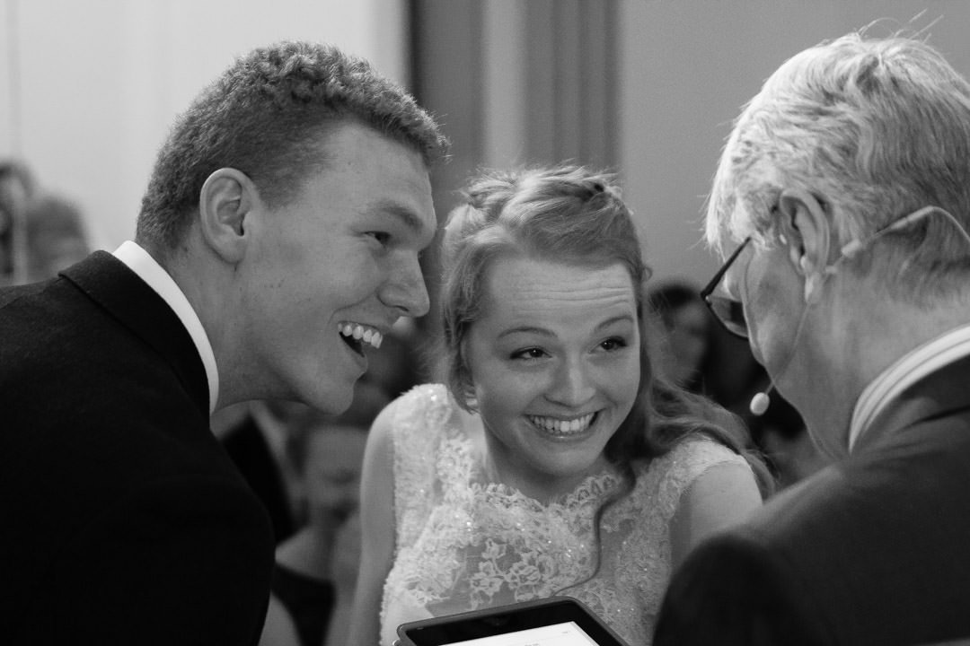 bride and groom share a laugh with the vicar at Walton Baptist church