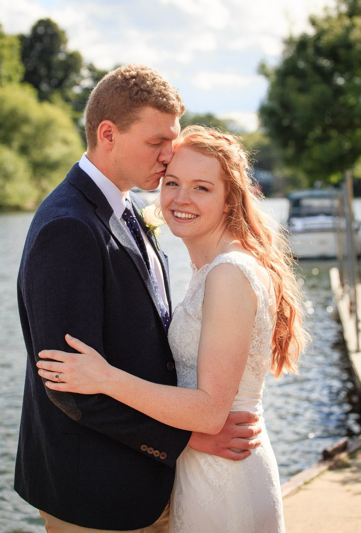 Groom kisses the bride's forehead by the river Thames after the wedding