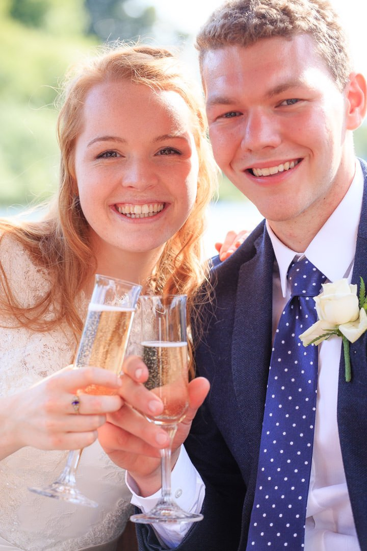 The bride and groom celebrate with champagne on a river cruiser on the Thames