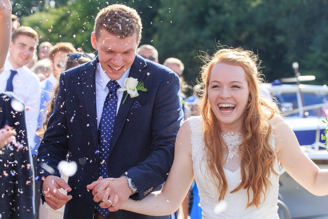 Bride and groom laugh as the confetti is thrown by the River Thames