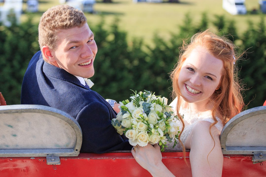 The bride and groom ride the ferris wheel on their wedding day at Apps Court Farm by the River Thames