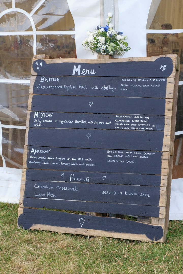 Wedding menu displayed on a pallet blackboard outside the marquee