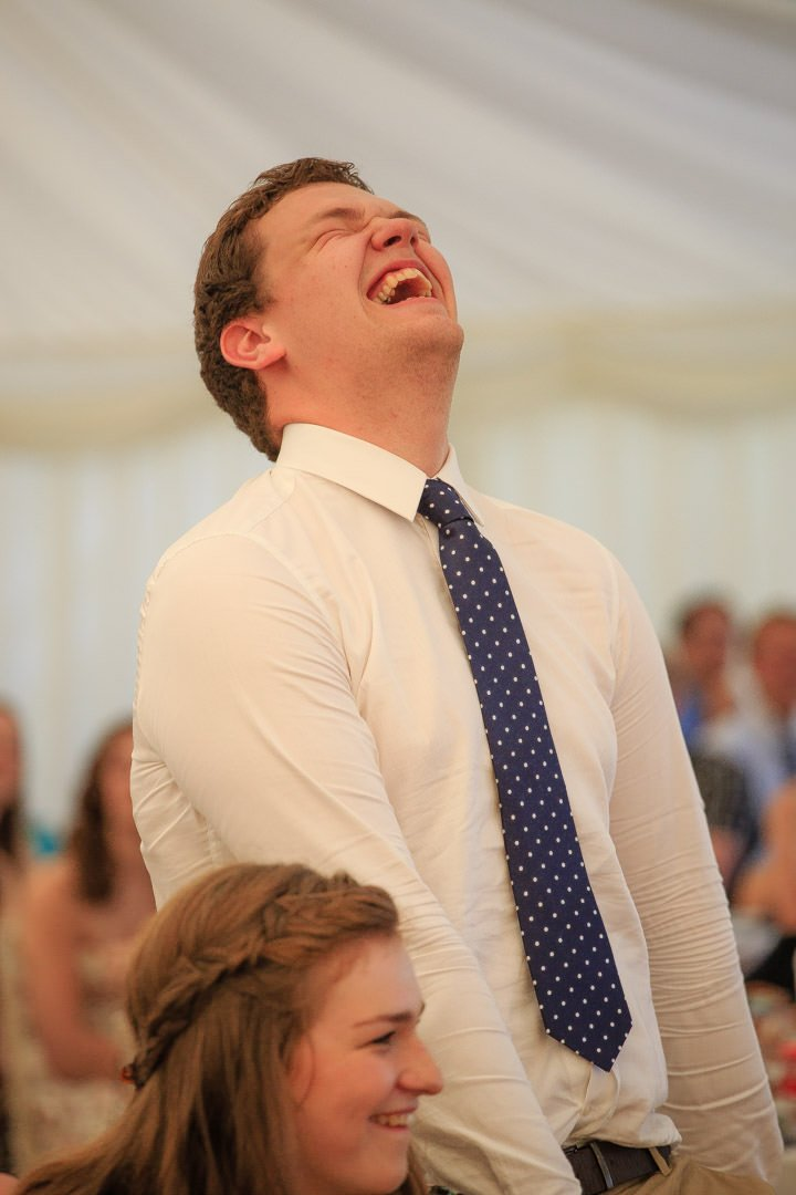 The Groom's brother stands up and roars with laughter during the wedding speeches