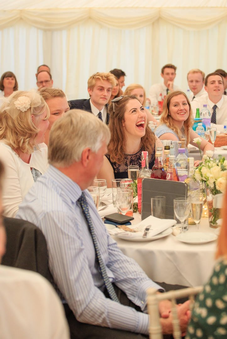 The chief bridesmaid laughs while all the guest watch during the speeches