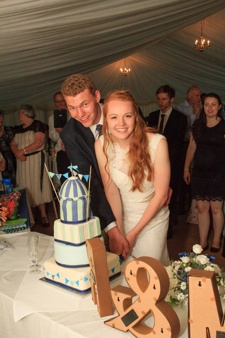 The bride and groom look at the camera as they cut the funfair wedding cake
