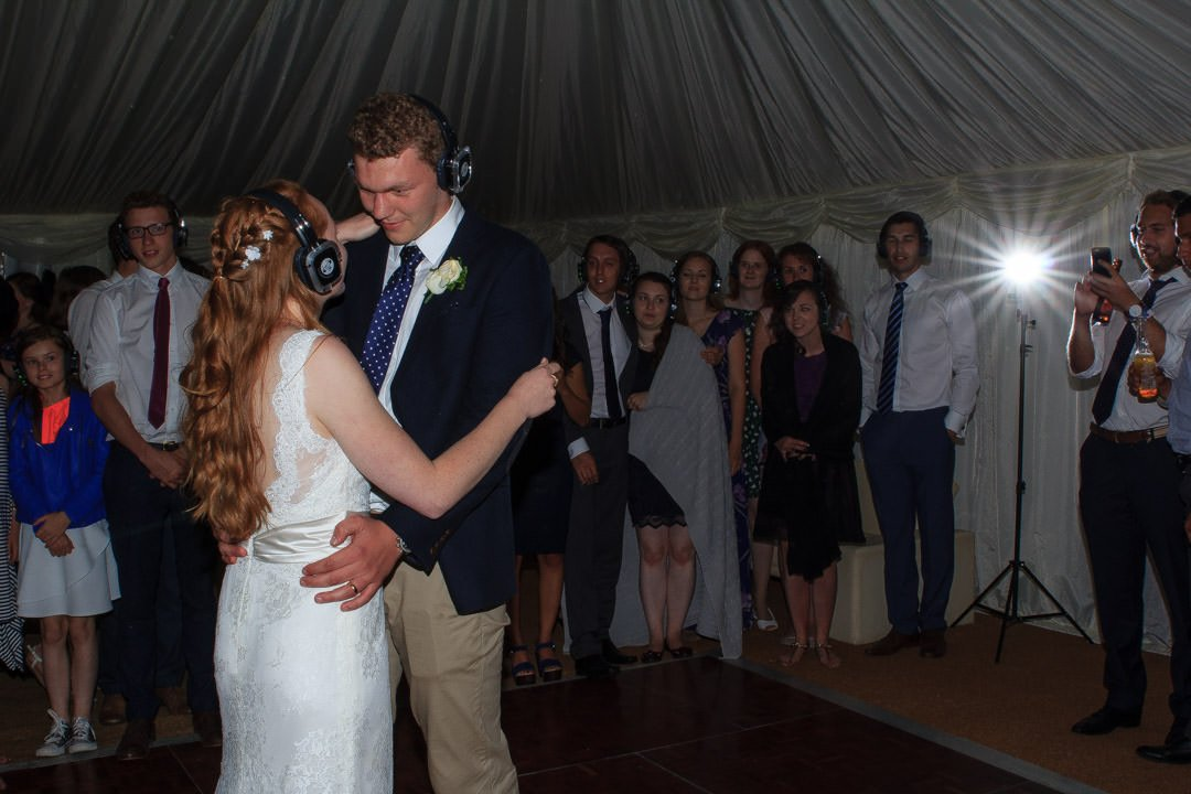 The bride and groom, wearing headphones, enjoy their first dance together during the silent disco and a flash goes off in the background