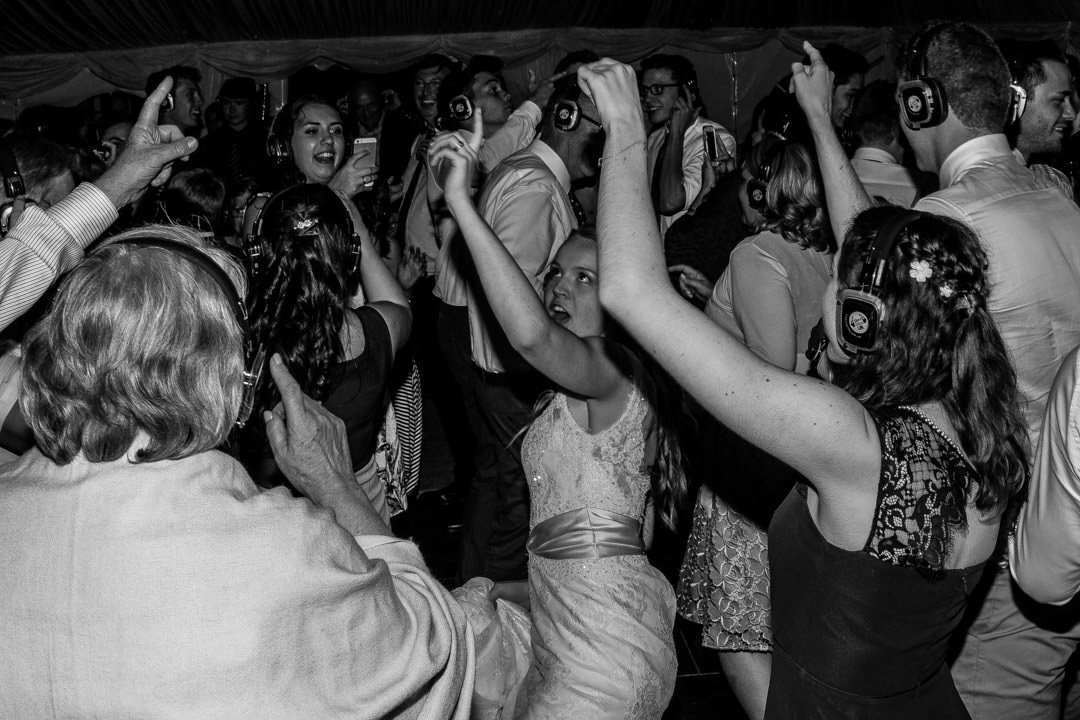 Black and white image of the bride and all of her friends dancing together with headphones on during the silent disco