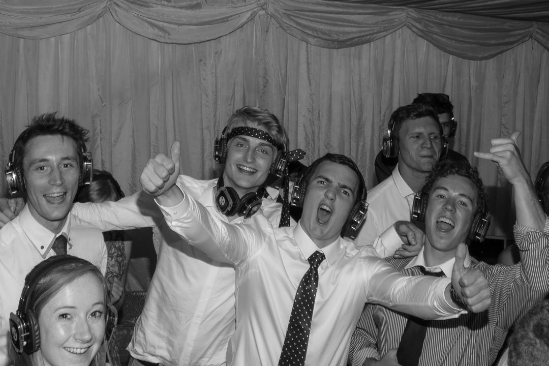 The groomsmen pose and dance wearing headphones during the silent disco