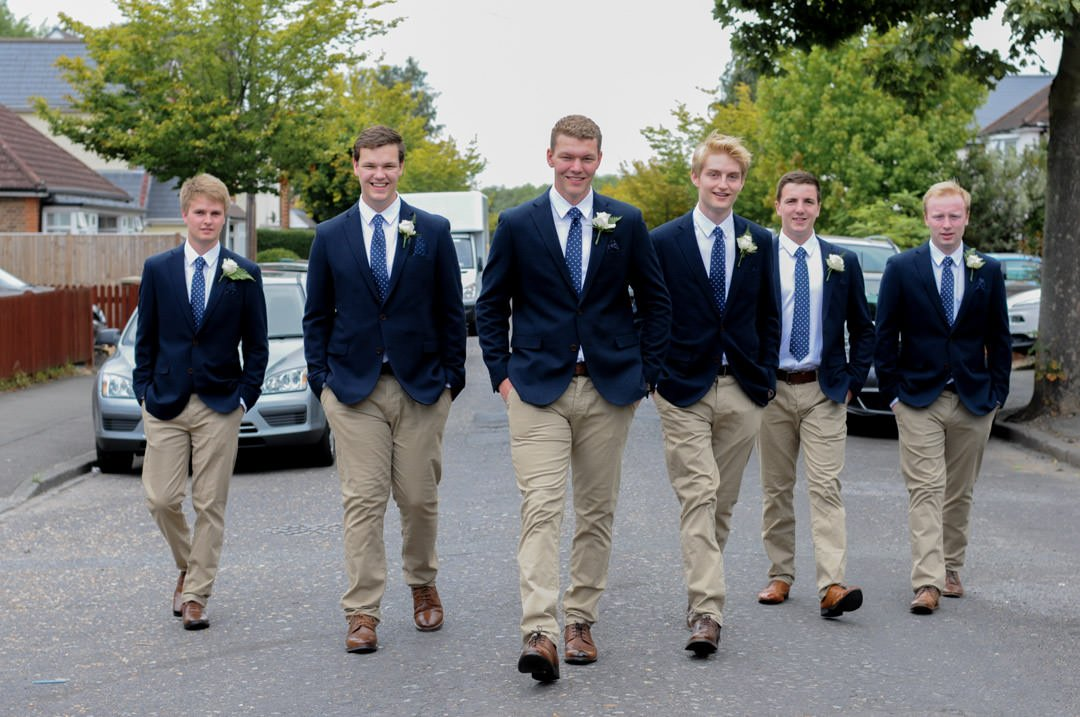 The groom and his groomsmen walk up the street in reservoir dogs formation
