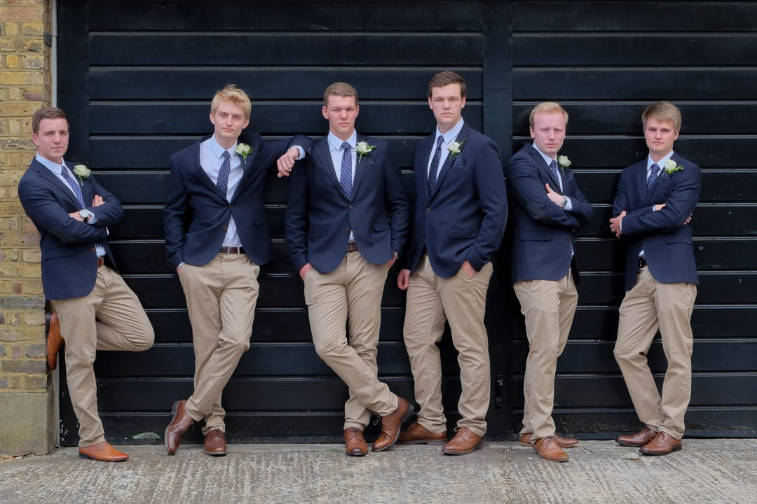 The groom and groomsmen pose in front of black garage doors