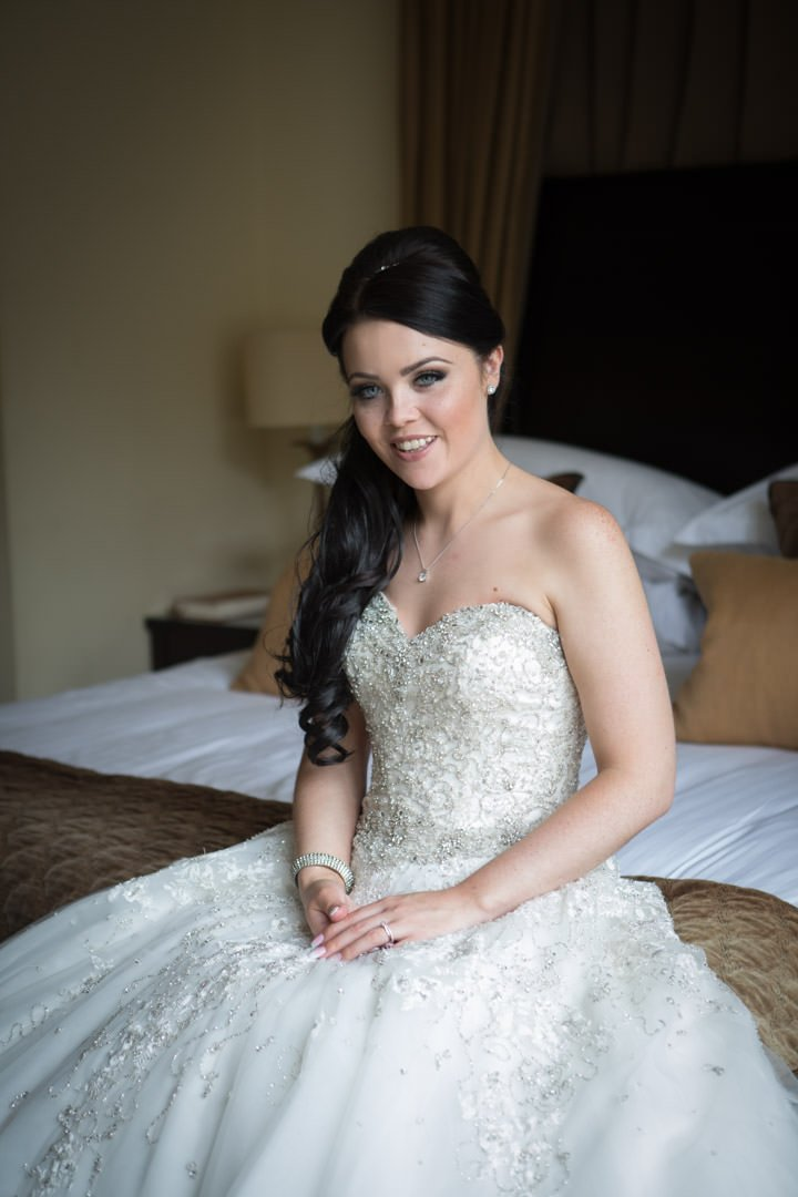 smiling bride sitting on the bed in the bridal suite at Frimley Hall Hotel