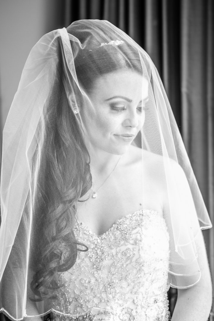 smiling bride with her veil over her face sitting on the bed in the bridal suite at Frimley Hall Hotel