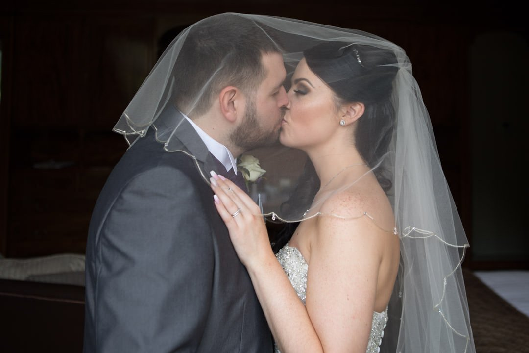 bride and groom kiss under her veil in the bridal suite at Frimley Hall Hotel