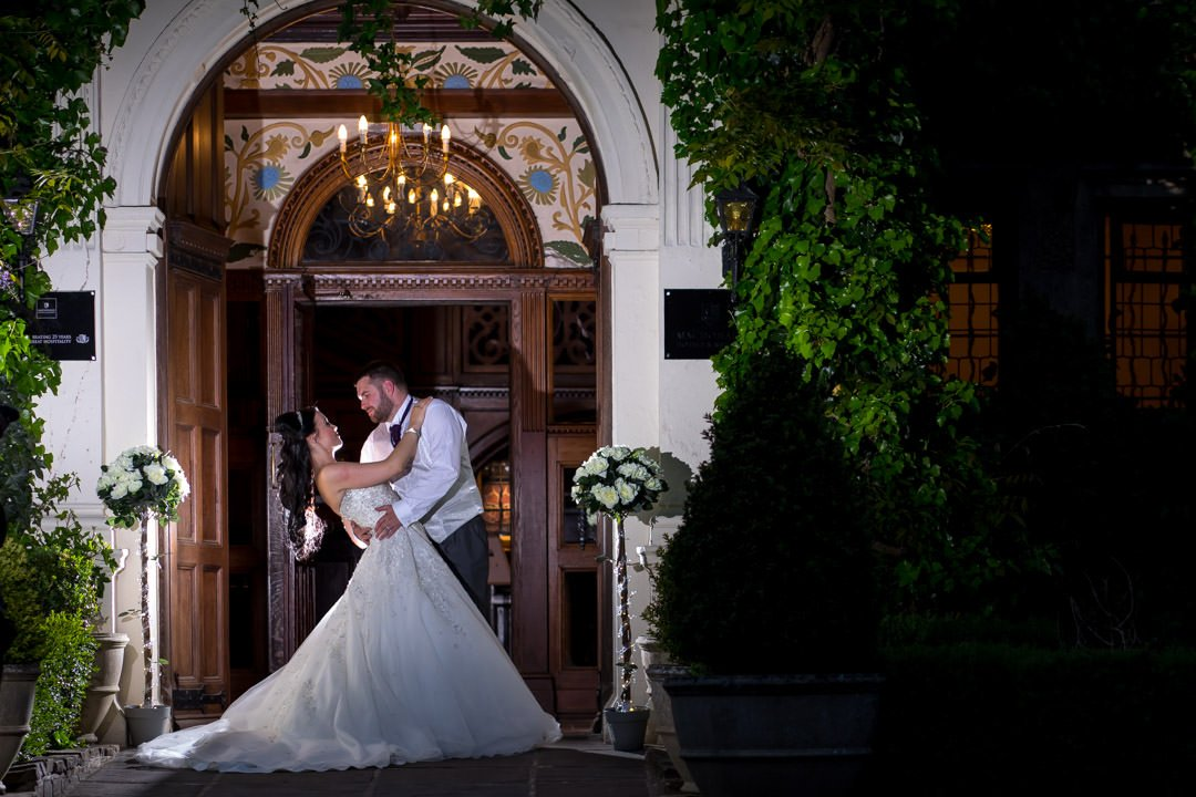 backlit bride and groom do the dip at Frimley Hall Hotel outside the main door at night