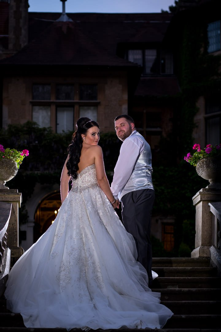 backlit bride and groom look back on the steps in front of Frimley Hall Hotel